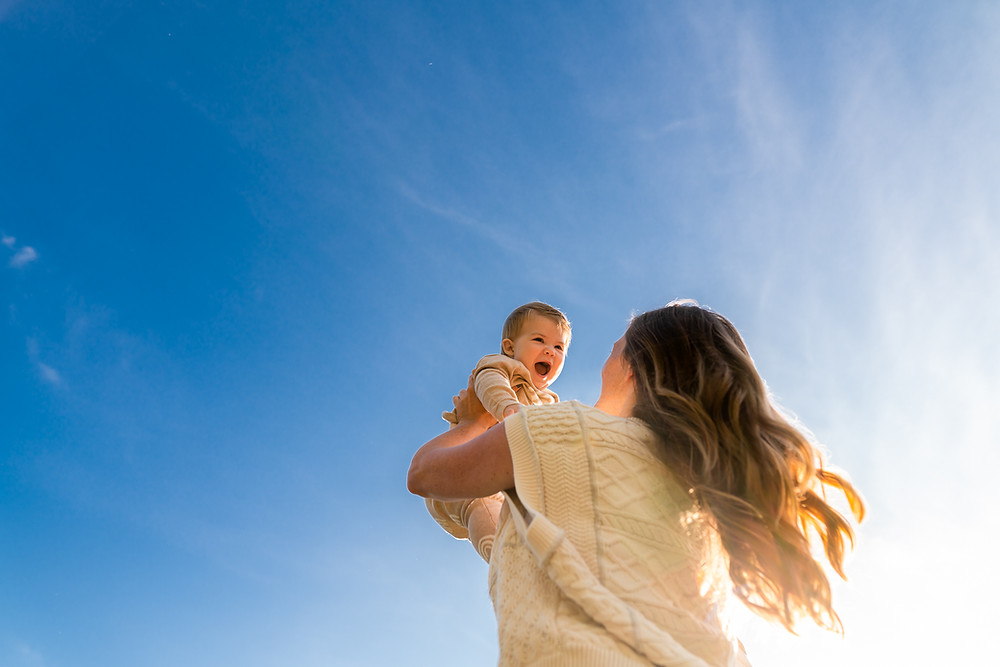 Mother lifting her happy baby into the air outdoors against blue skies