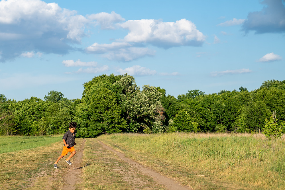 A boy running down a path at a park on a beautiul day with blue skies and clouds in Kalamazoo, Michigan