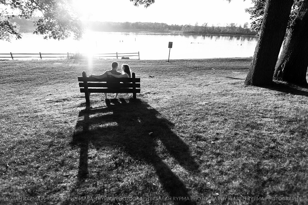 Couple sitting together on a bench at engagement session