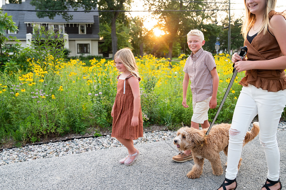 Children walking their new puppy on a leash outside