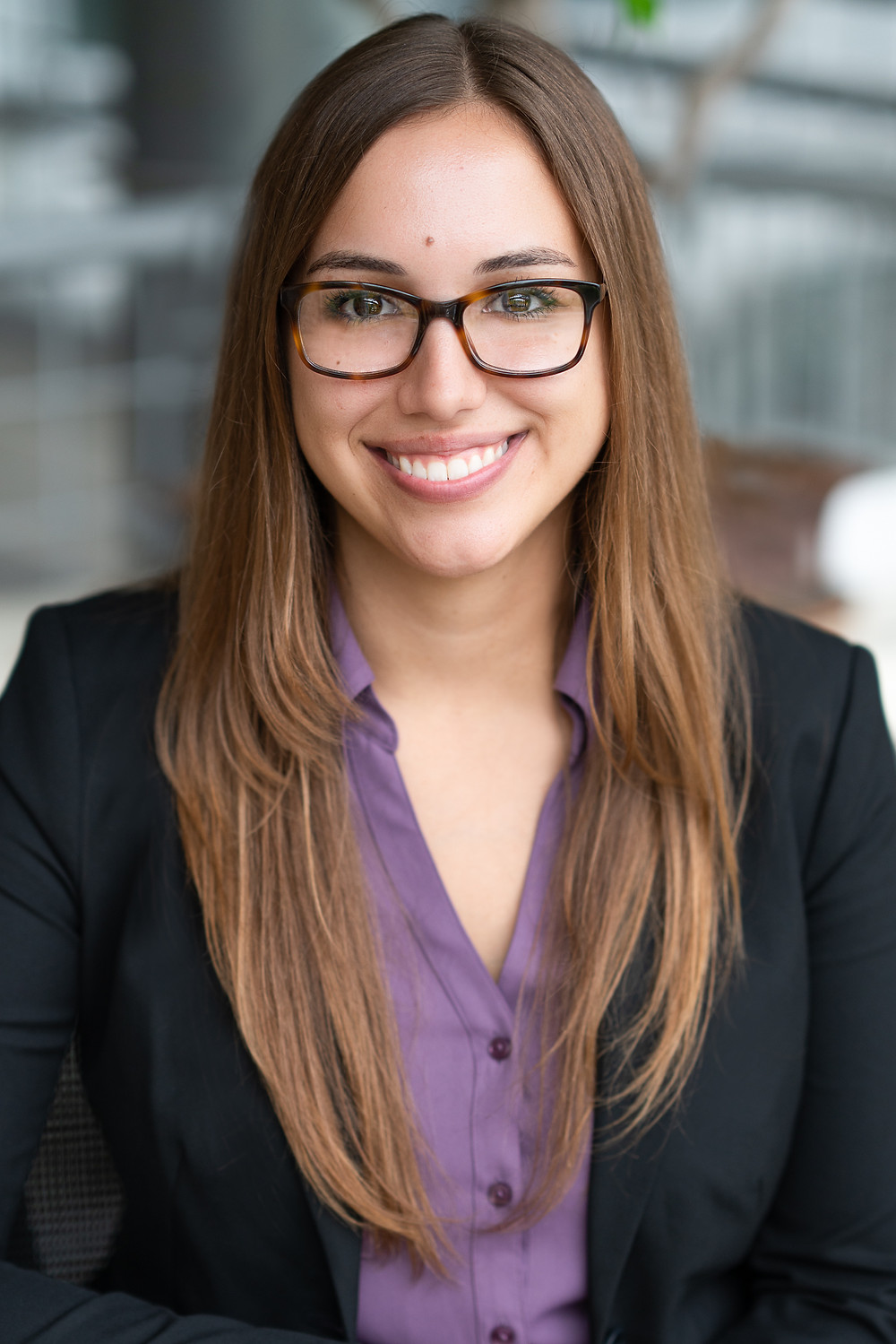 A woman wearing glasses smiling for commercial headshot portrait