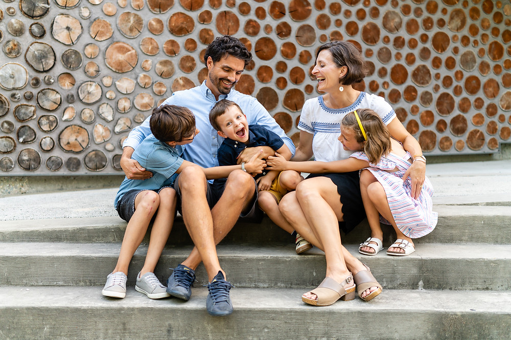 Happy family sitting together on steps to a building and laughing