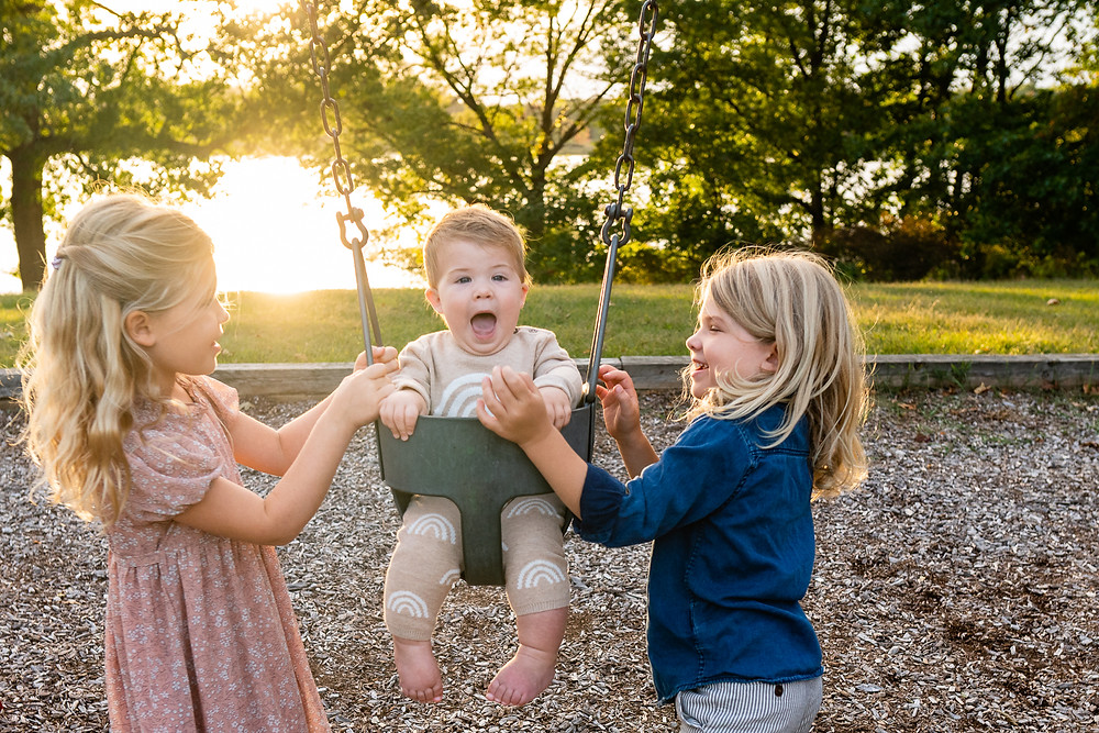 Young children pushing their baby brother in a swing outdoors