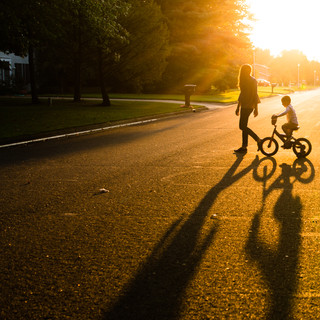 Silhouette of a Young Boy Riding his Bike with his Mother
