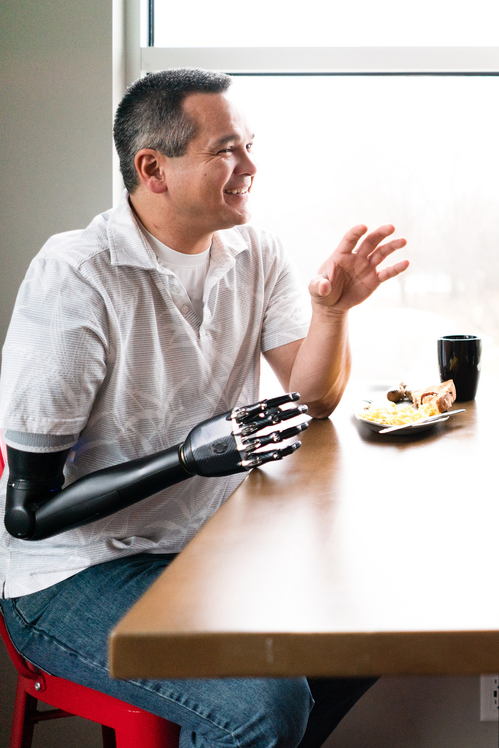 Man with a prosthetic arm at a restaurant talking to his wife