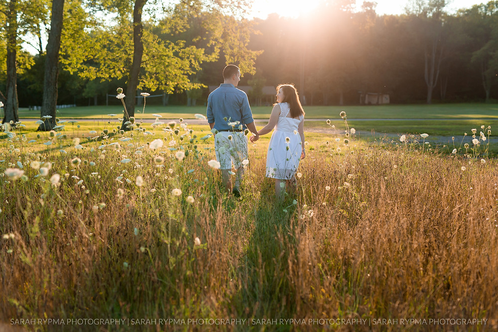 Couple walking in a field at engagement session