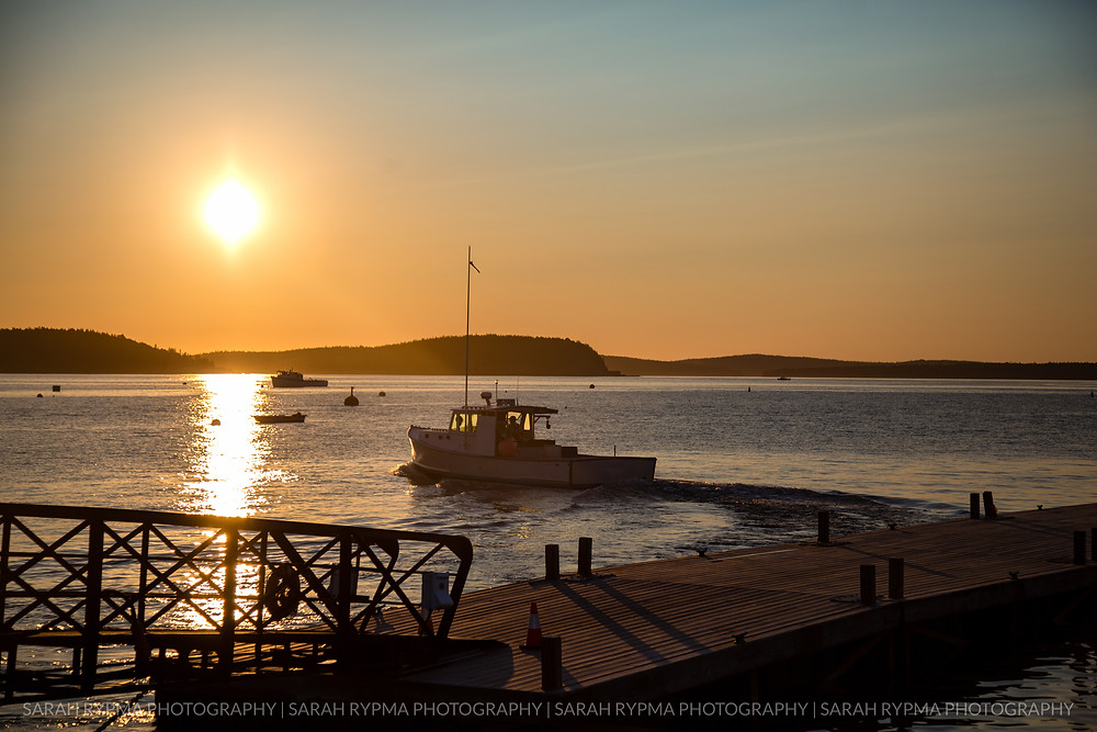 Lobster boat departing harbor at sunrise
