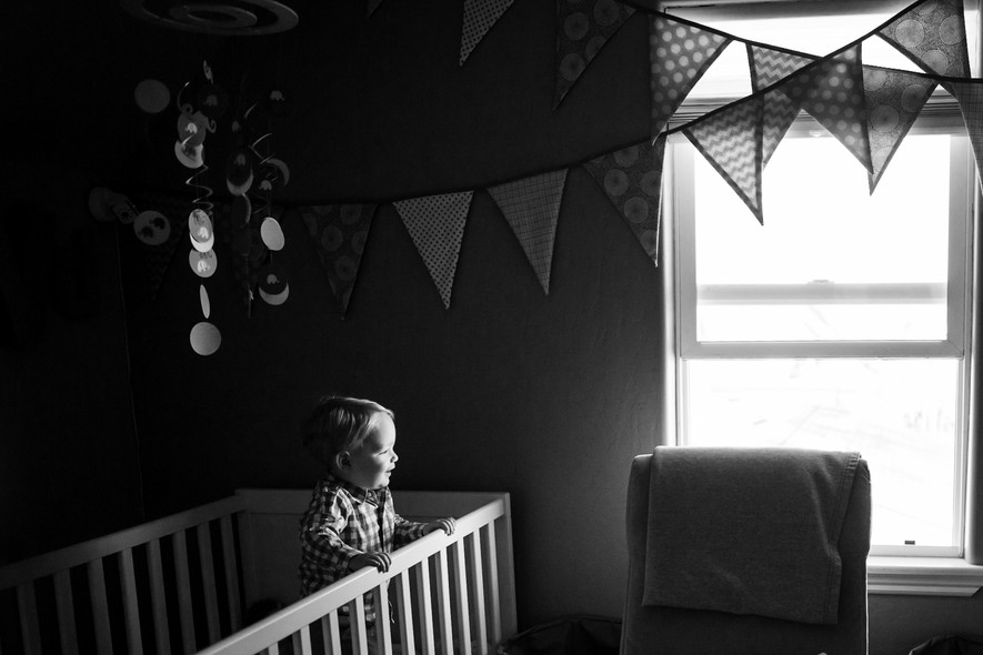 Denver Family Photographer, Sarah Rypma, photographs a boy in his crib looking out the window.