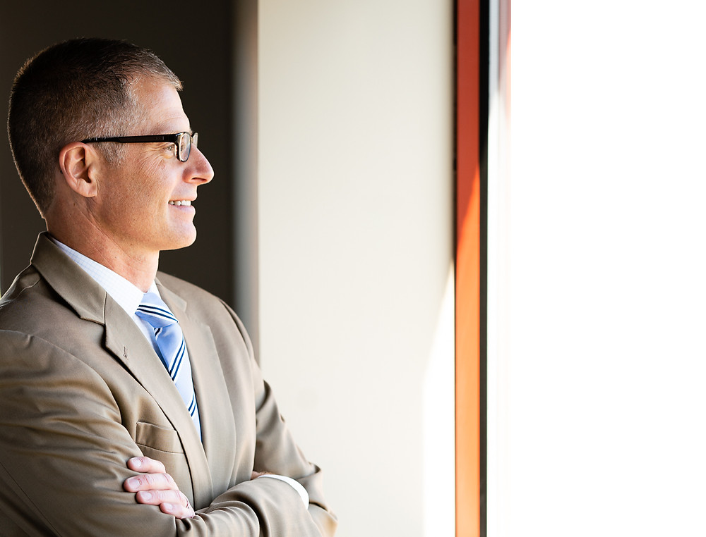 An older man wearing glasses and a suit looking out the window of his office