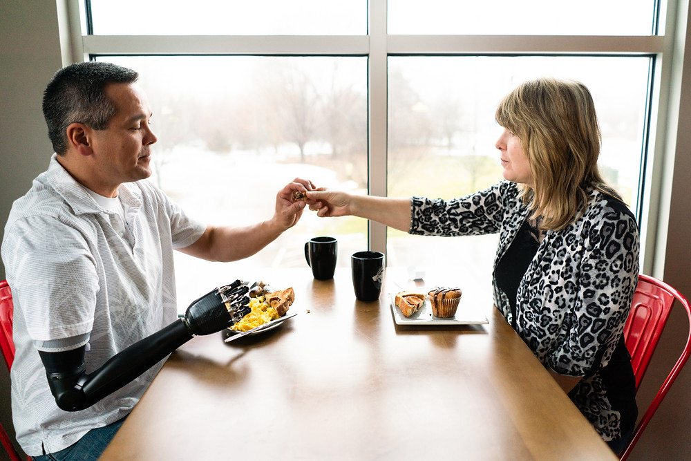 Man with a prosthetic arm eating breakfast at a restaurant with his wife
