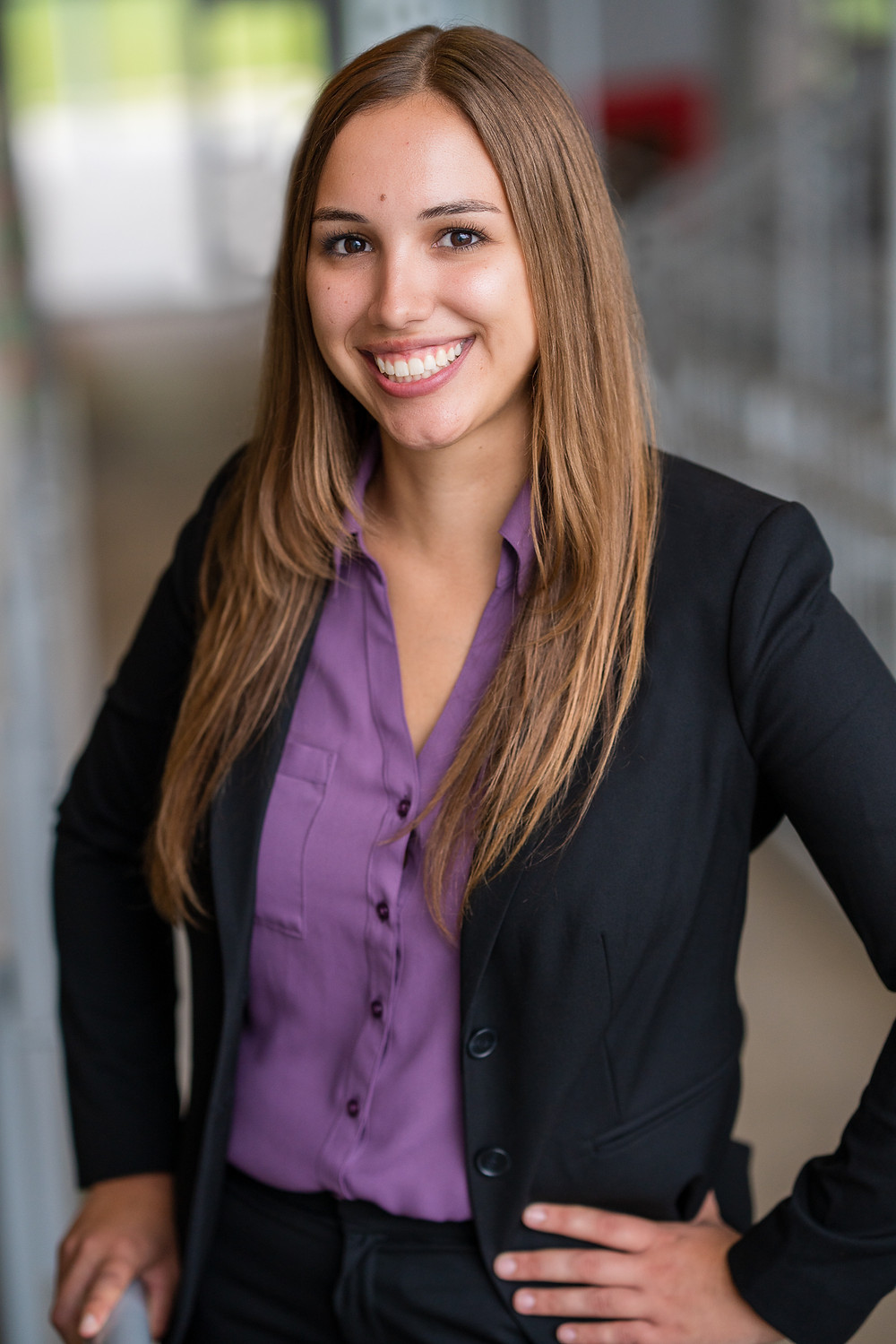 A business woman wearing a suit with a purple shirt smiling for a professional portrait