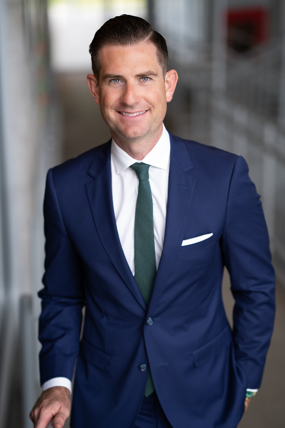 A man wearing a suit and tie poses for his professional headshot