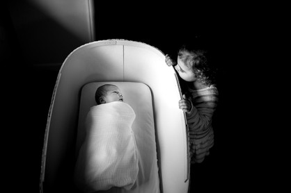 Big Sister looks at newborn sister
