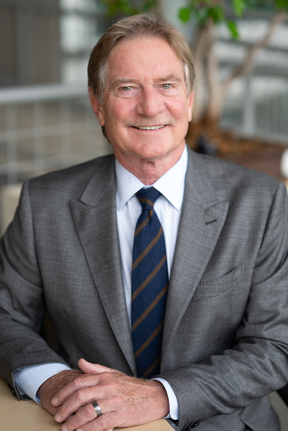 An older man dressed in a business suit and tie smiling at camera for professional portrait