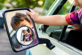 Boy looks at image in side mirror