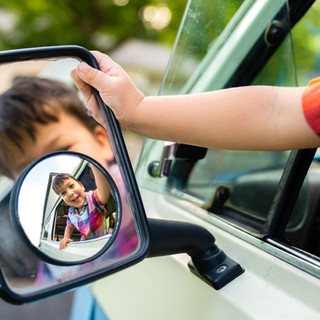A Young Boy Looks at His Reflection in a Car Mirror