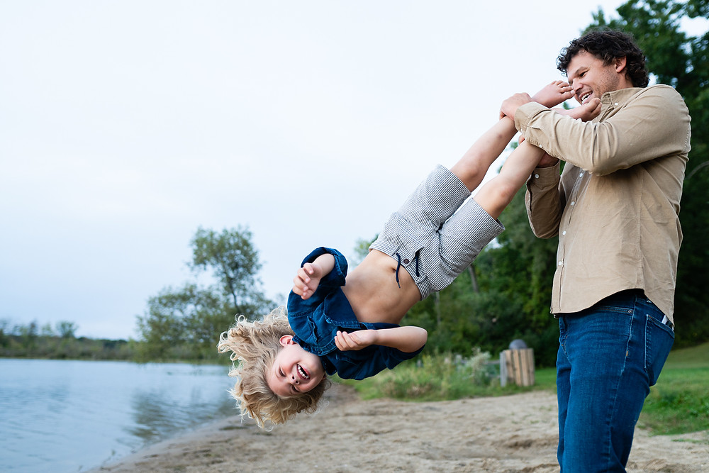 Father Twirling his son outdoors on a beach in Kalamazoo, Michigan