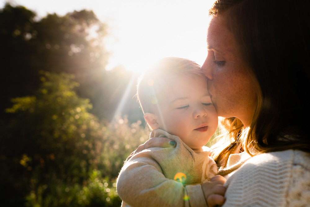 Mother kissing her baby with sunlight streaming through