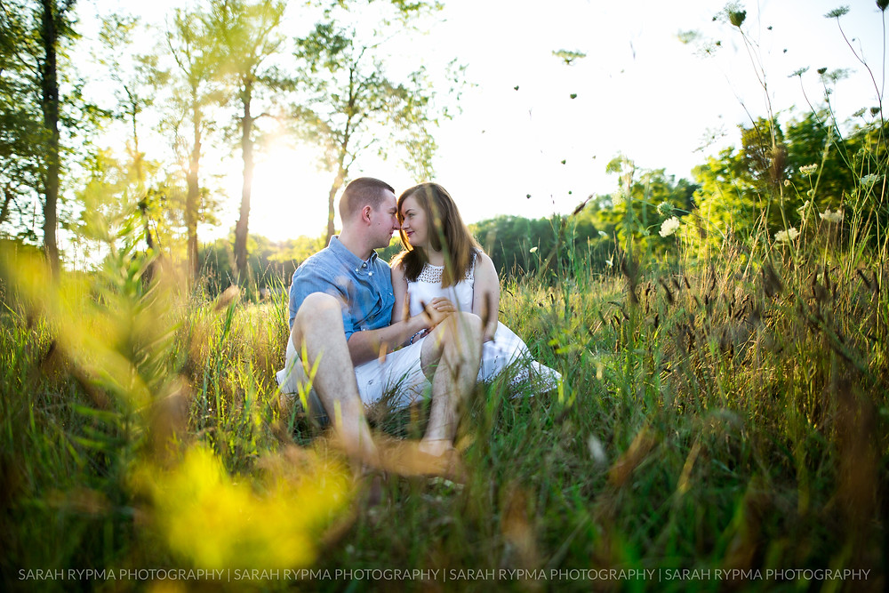 Couple sitting in a field at engagement session