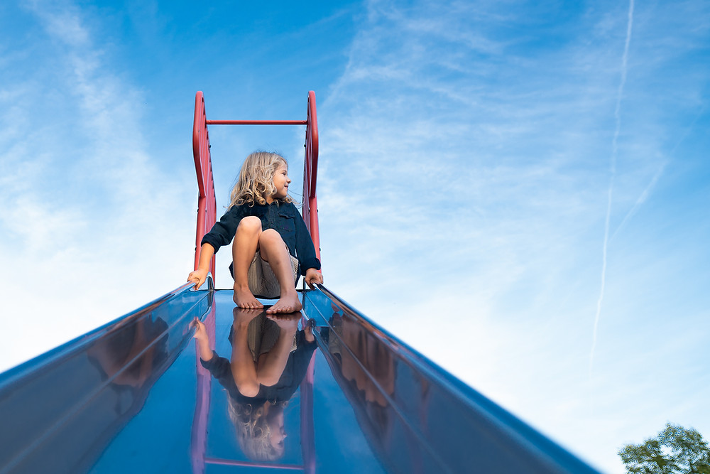 Young boy sitting at the top of a slide outdoors at a playground