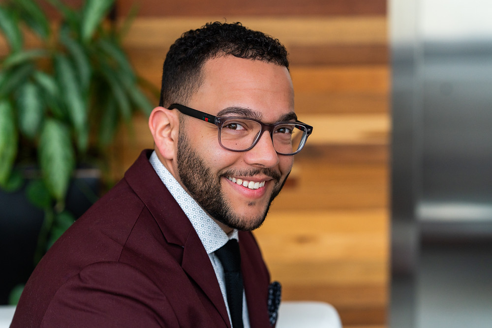 A young business professional wearning glasses looking at camera for professional headshot