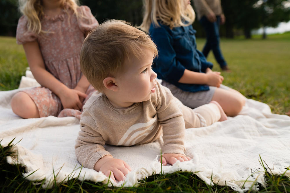 Baby laying on a blanket looking off into the distance
