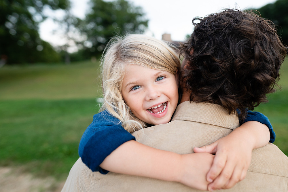Happy boy hugging his father while looking at the camera