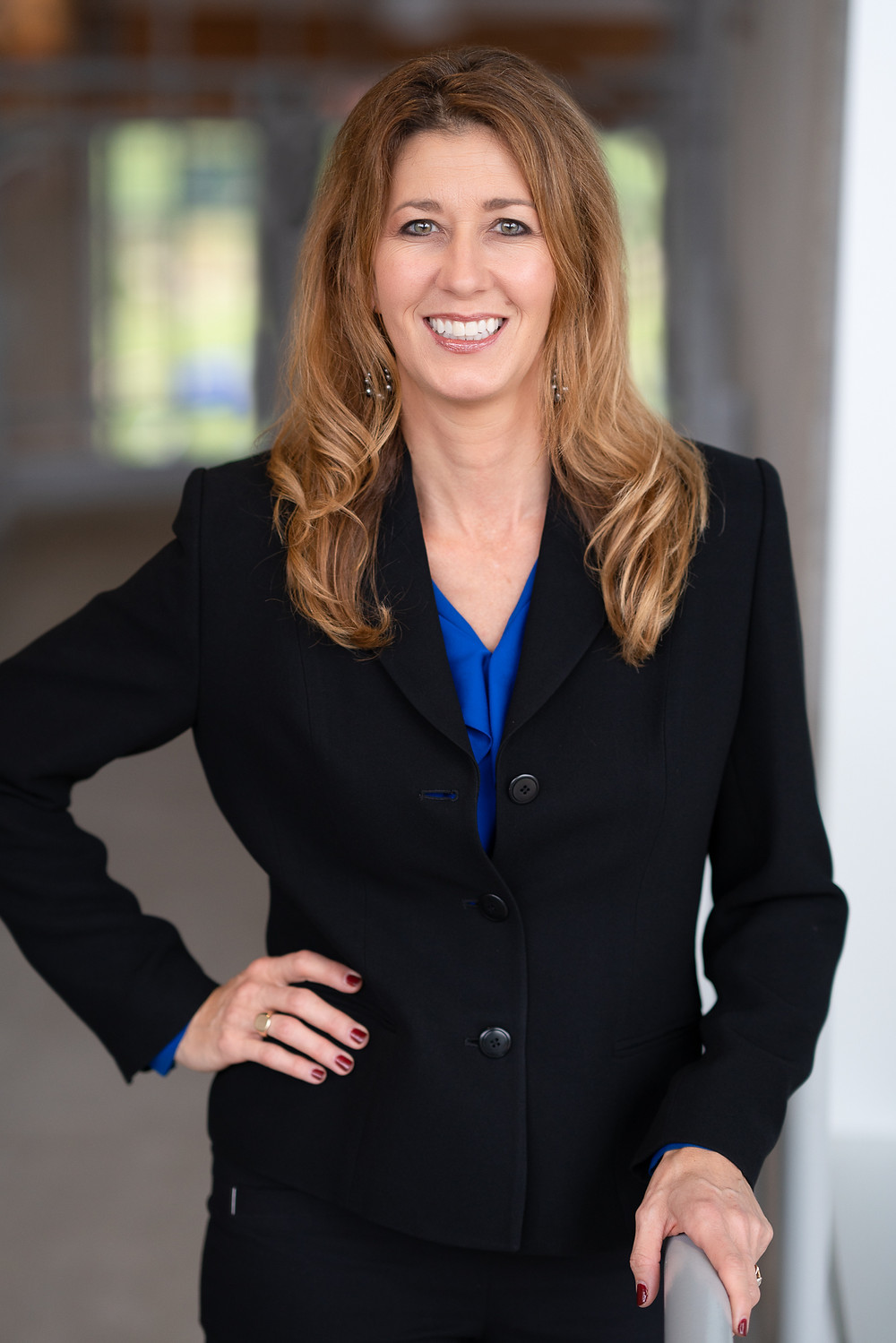 A business woman dressed in a suit smiling at camera for a professional portrait