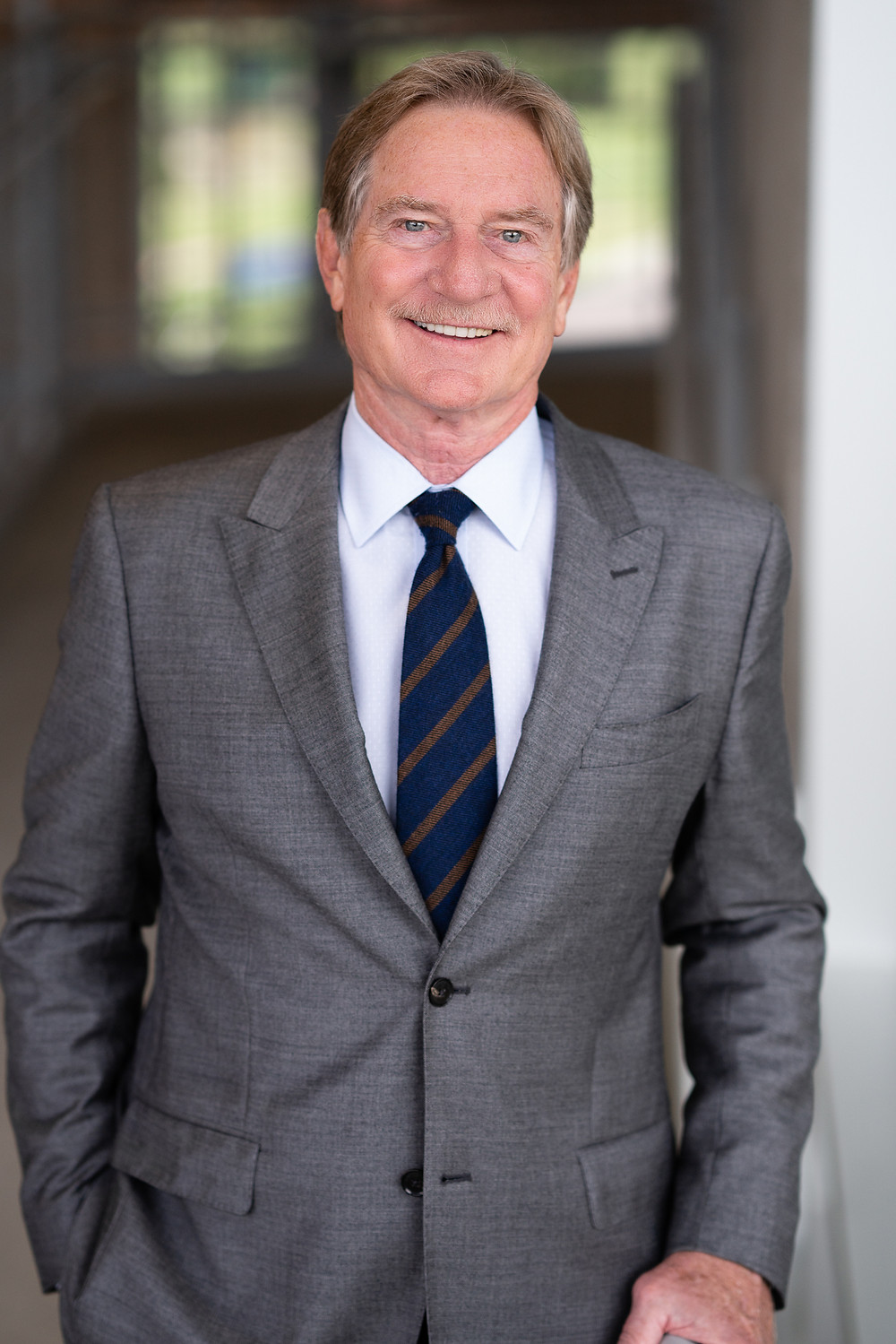An older man in a business suit and tie smiles for his commercial headshot portrait