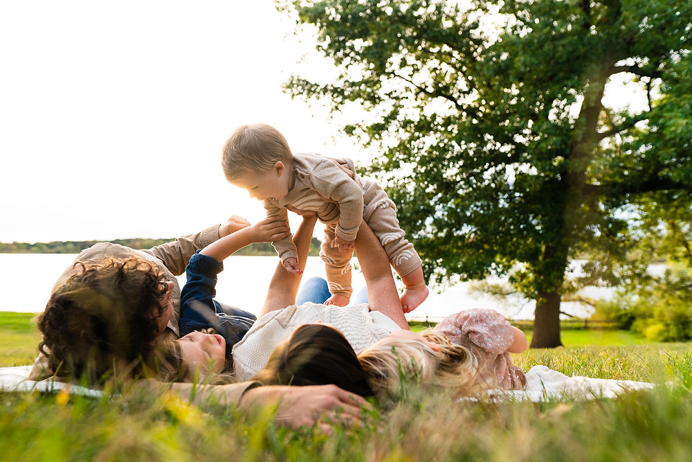 Family laying on a blanket holding a happy baby in the air