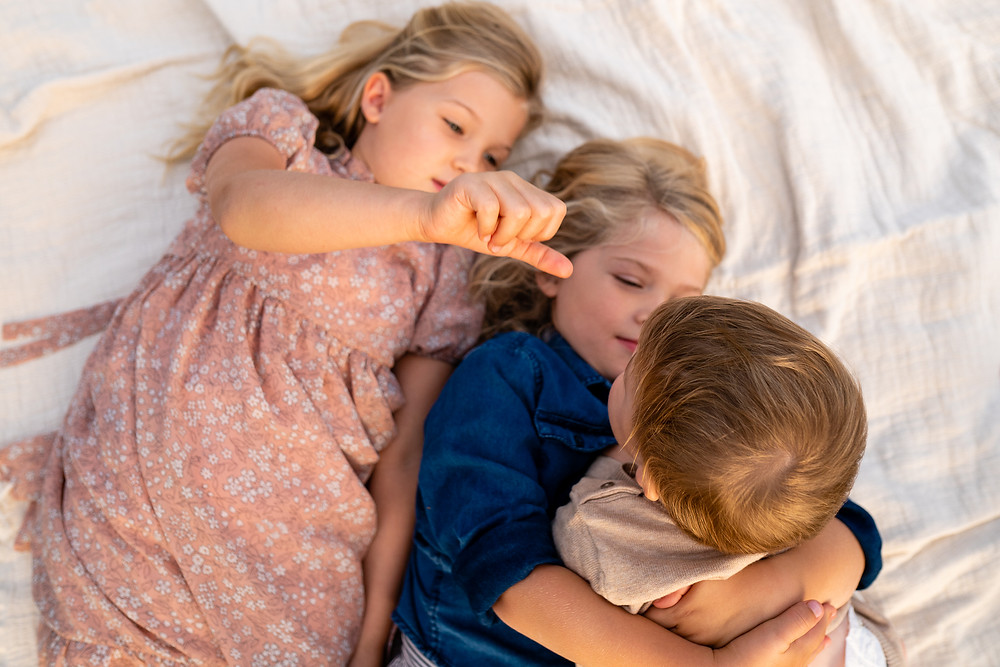 Children laying on blanket outdoors