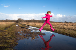 Girl in pink jumping over a puddle