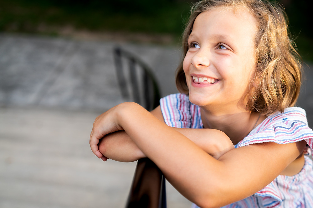 Candid portrait of a young girl smiling and looking away