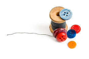 Thread bobbin and buttons isolated on wh