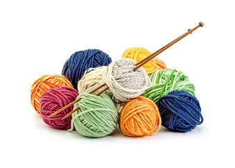 Colorful balls of yarn and wooden needle