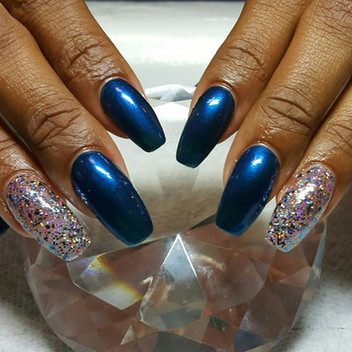long ballerina acrylic nails with blue polish and glitter accents.