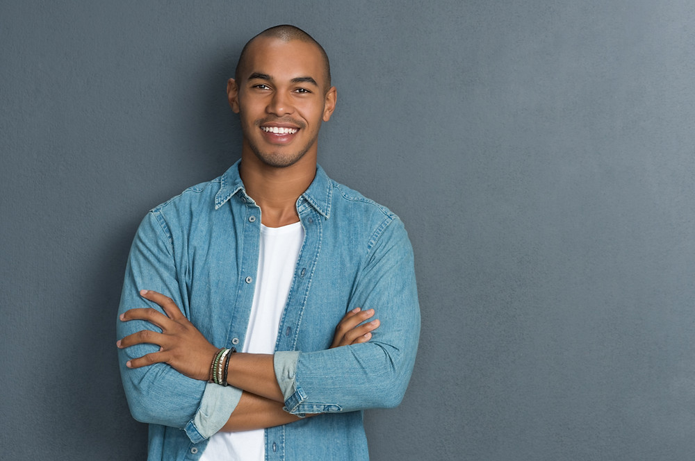 Smiling young man in blue denim jacket. Straight and white teeth