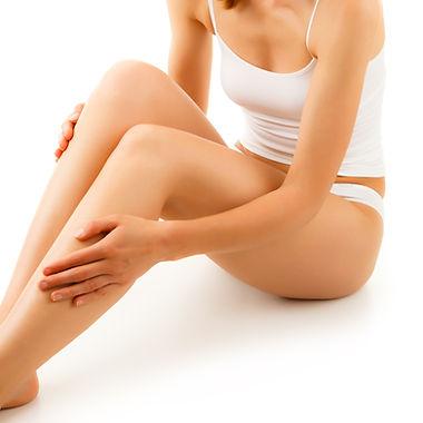 Woman massaging legs sitting on white ba