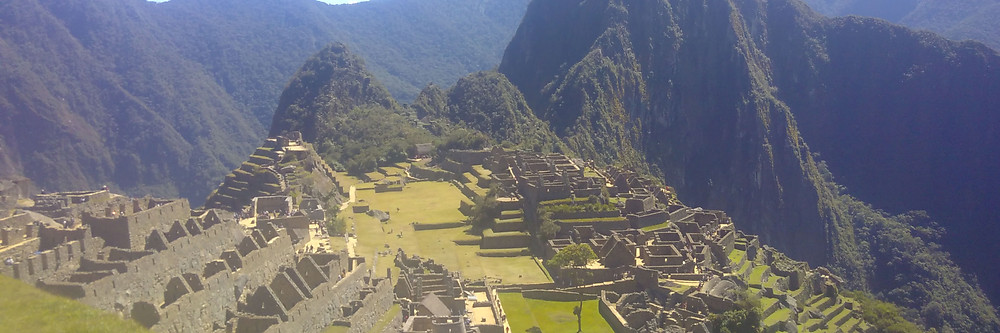 Photograph looking out over the unbelievable architectural feat of Machu Picchu, nestled in the mountains