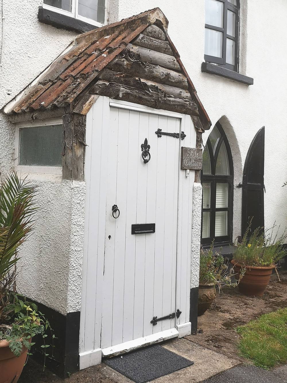 Stile Cottage front door featuring gothic style detailing and windows