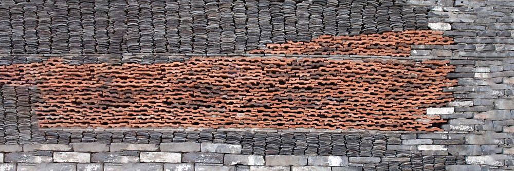 Stacked tiles, bricks and slate in a merge between reclaimed and new construction
