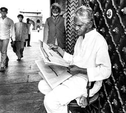 Man reading newspaper outside of Mosque