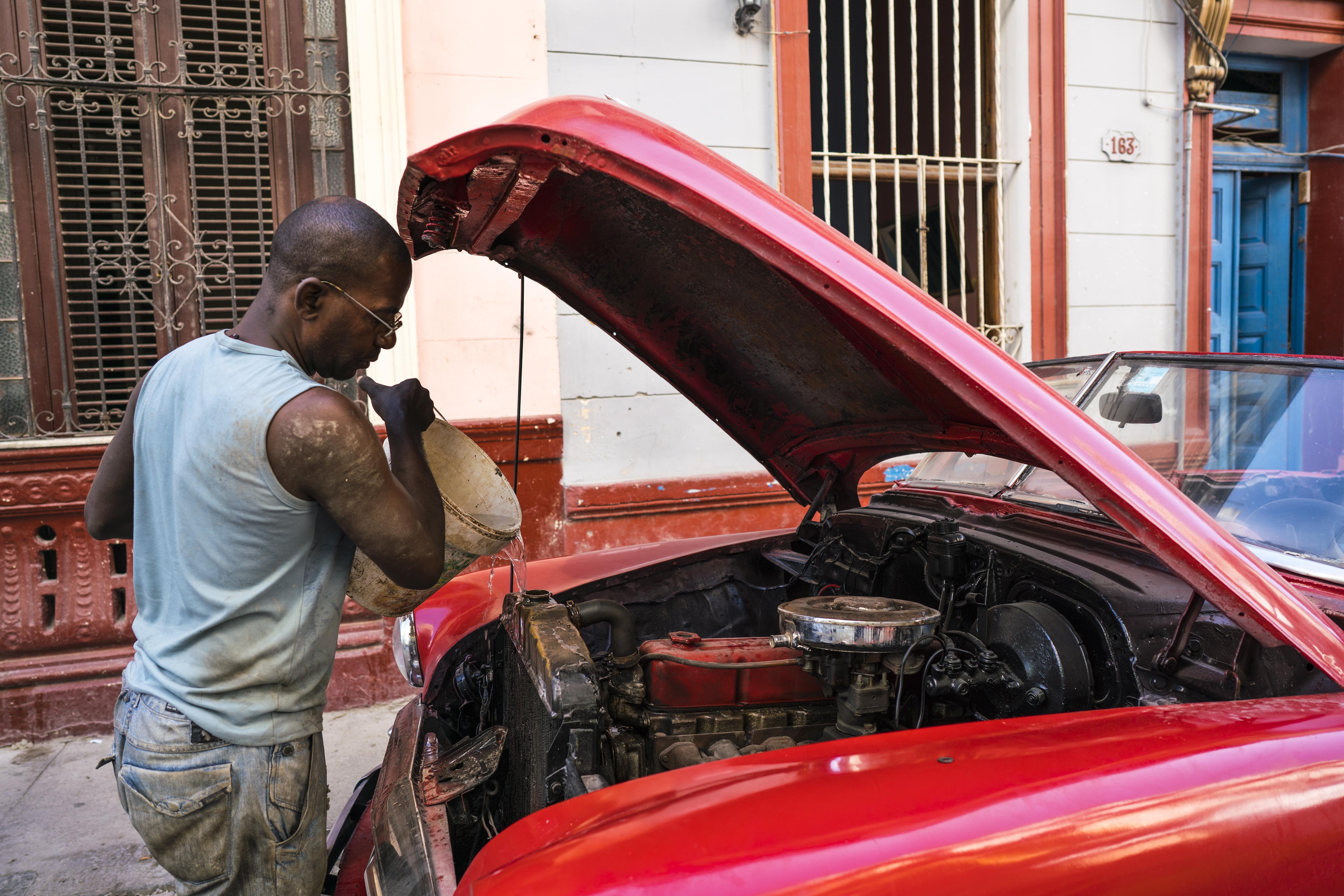 Man puttiing water in car radiator