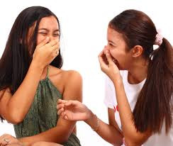 two young women laughing at the bad smell