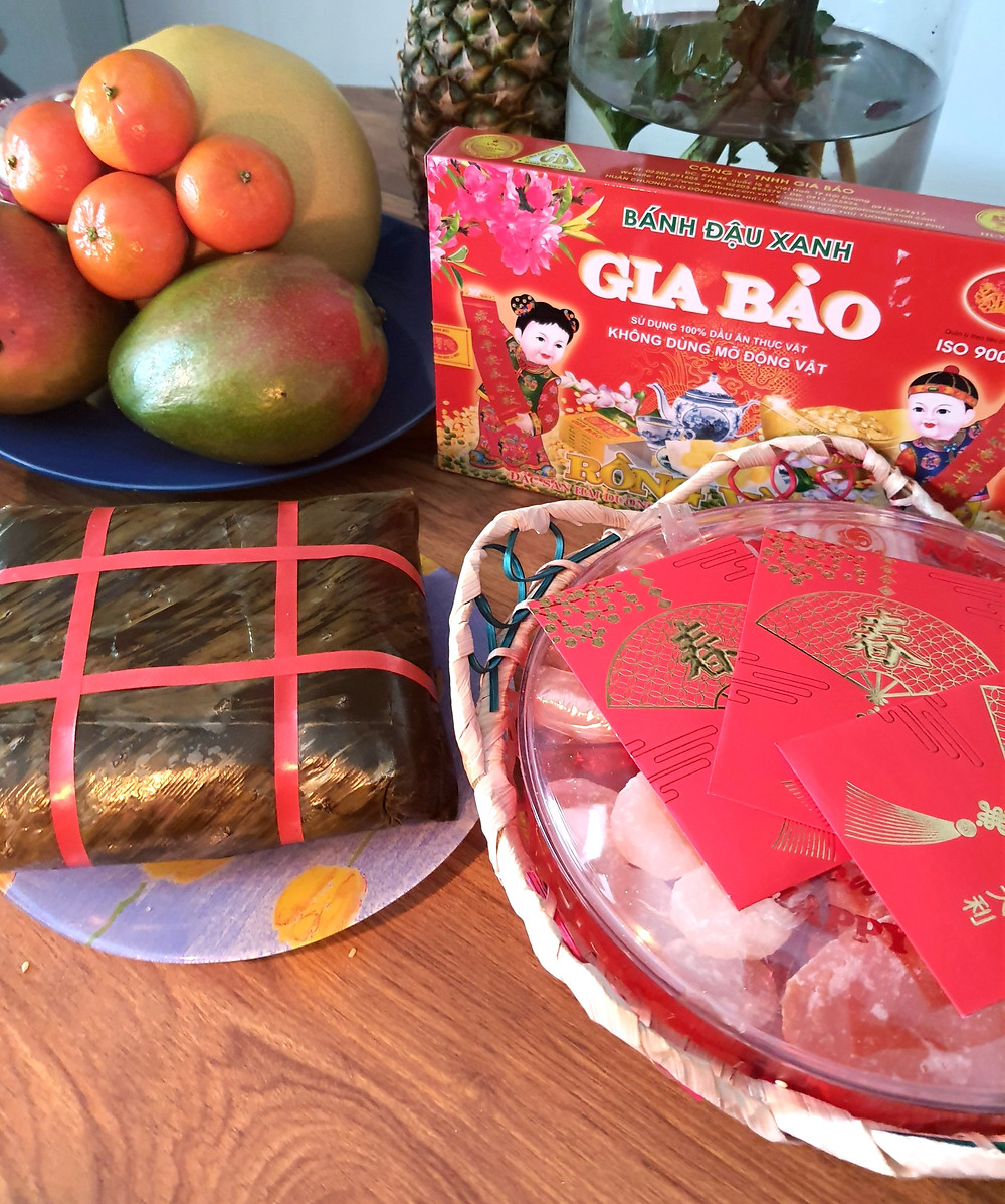 fruits exotiques, banh chung, confiseries vietnamiennes et enveloppes rouges disposés sur une table pour offrande lors du nouvel an lunaire