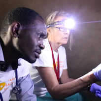 Dr. Daniel Antoine examines a mobile clinic patient in Mapou with HHP executive director Louise Lindenmeyr.