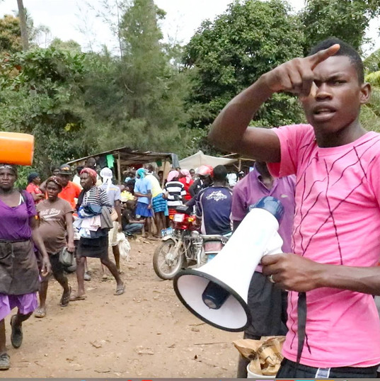 A promoter announces HHP's mobile clinic with his megaphone at the Wednesday market in Mapou.