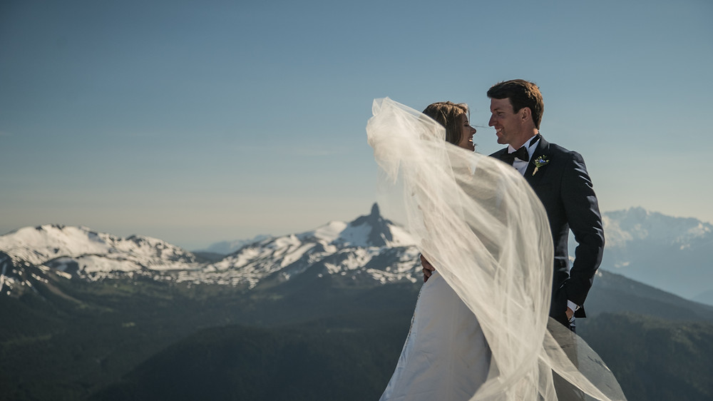 Couple smiling on peak of Whistler Blackcomb during couple photo session