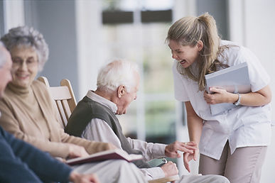Nursing assistant laughing with elderly patients.