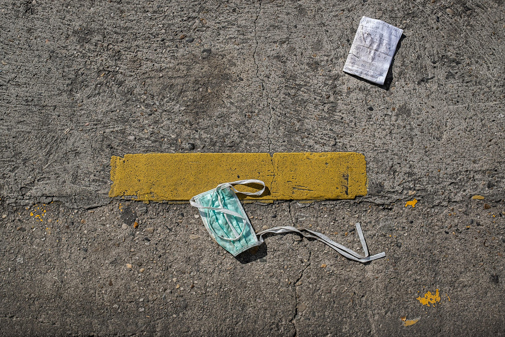 A dirty mask and piece of paper in the middle of the road